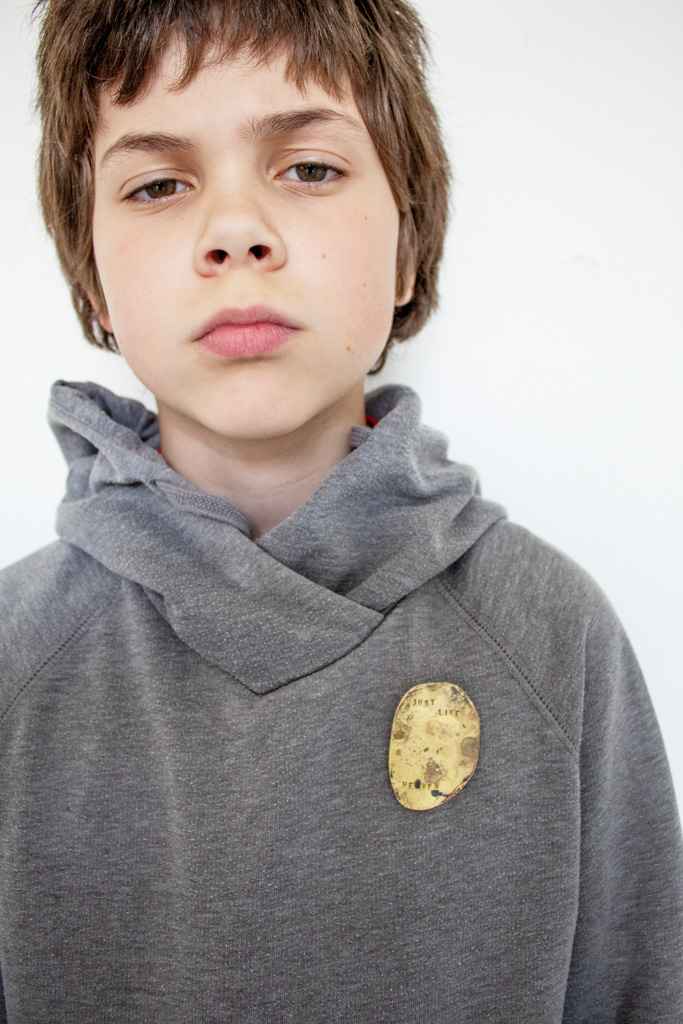 Young boy with grey sweater, brooch attached to sweater